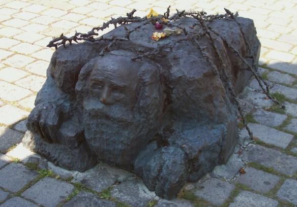 Kneeling Jew cleaning sidewalk at base of Monument against War and Fascism by Alfred Hrdlicka, Albertinaplatz, Vienna